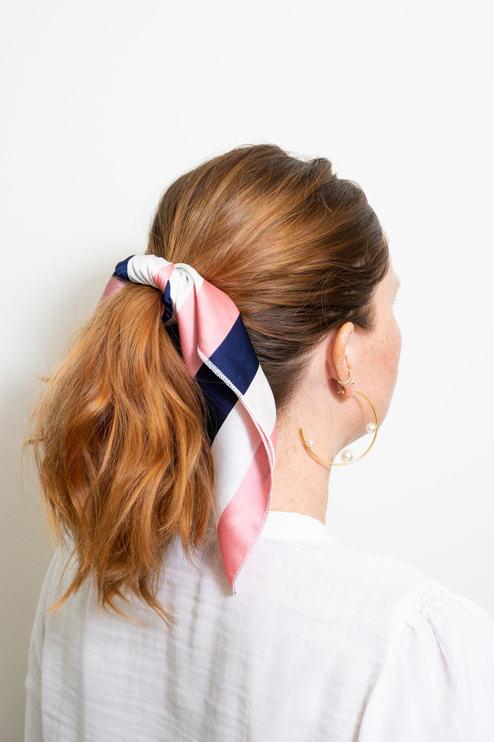 red head with pink navy white striped hair scarf tied in hair ponytail hoop earrings Janna Conne