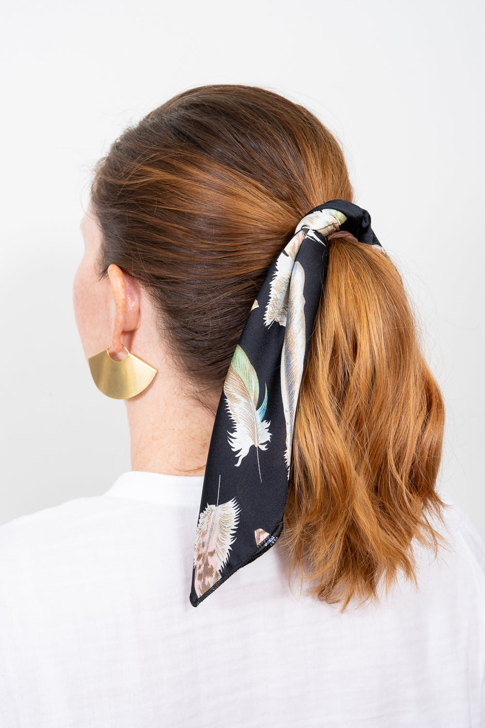 red head with black print scarf tied in hair ponytail gold hoop earrings Janna Conne