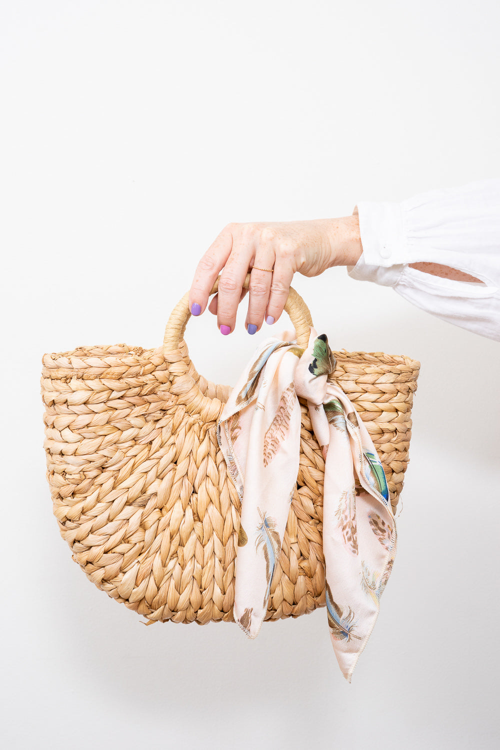 hands holding straw handbag with scarf tied on handle janna conner