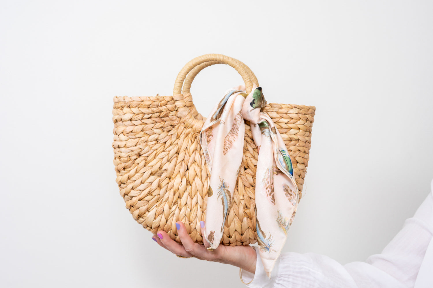 natural raffia straw rattan tote hand bag with pale blush scarf held in hand Janna Conner