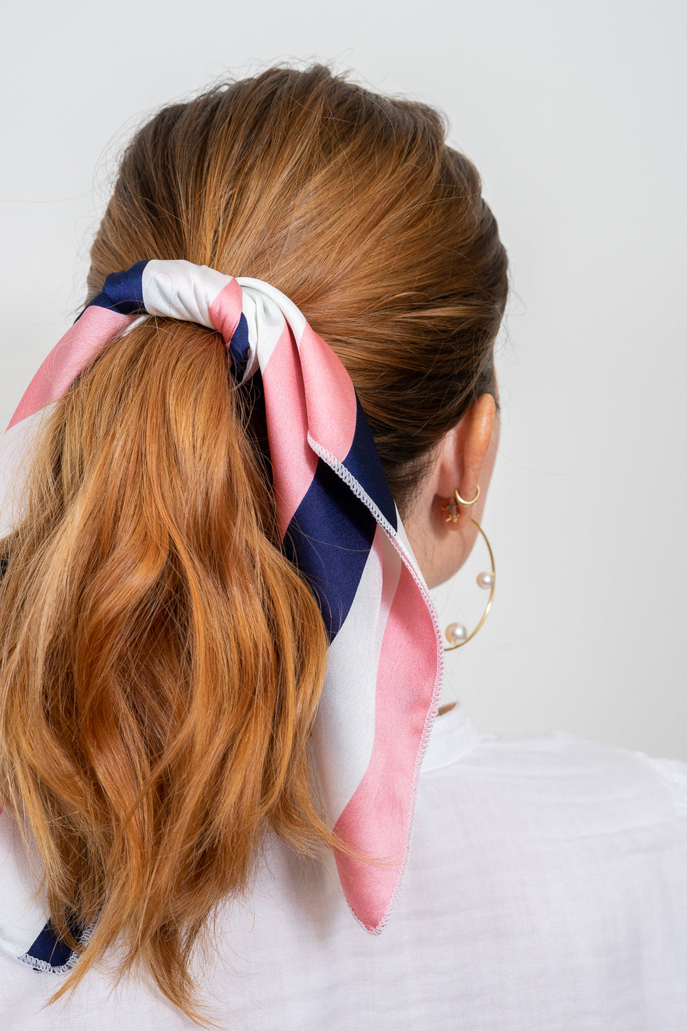 red head with pink navy white striped scarf tied in hair ponytail hoop earrings Janna Conne