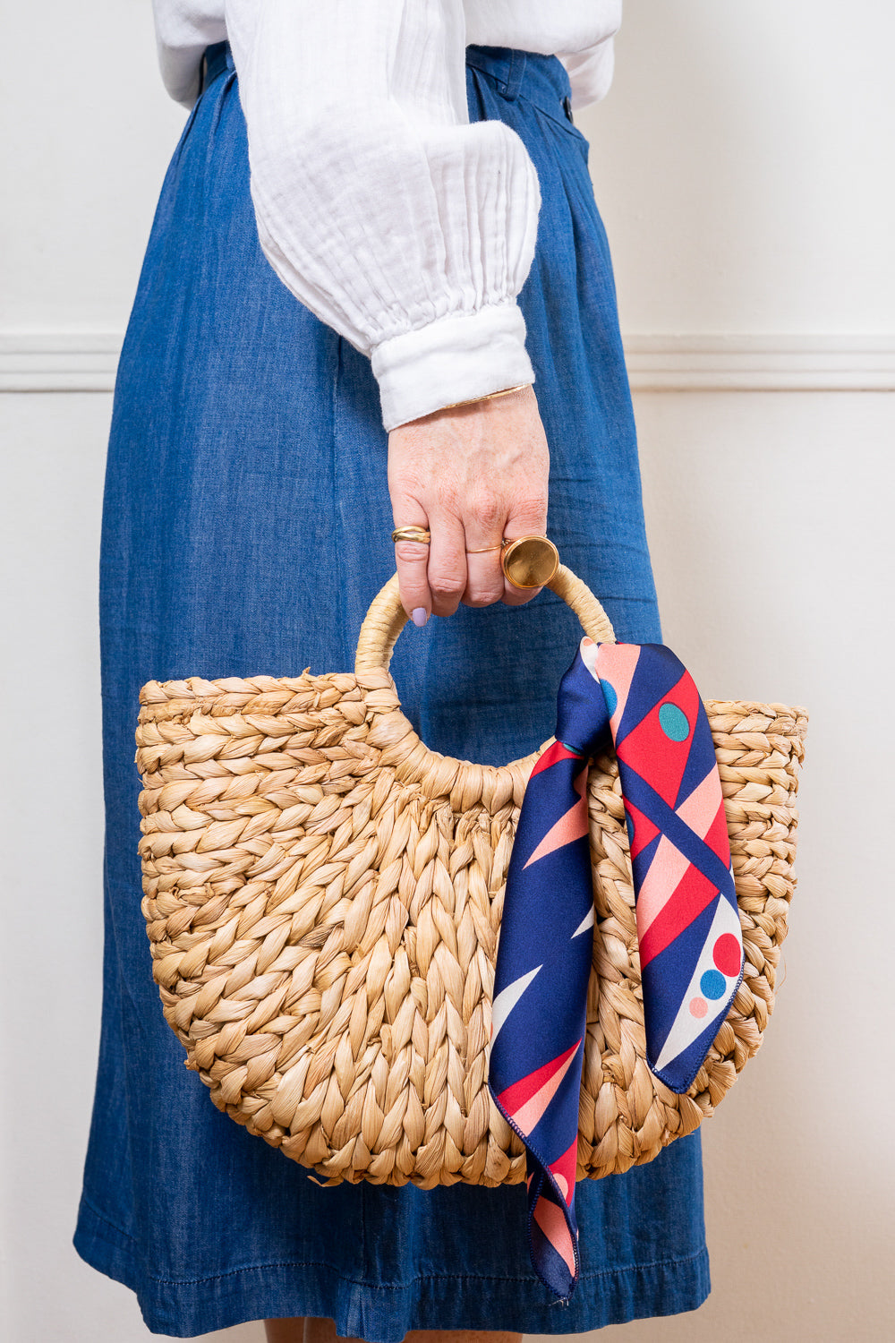model holding straw hand bag with red blue print scarf tied on handle janna conner