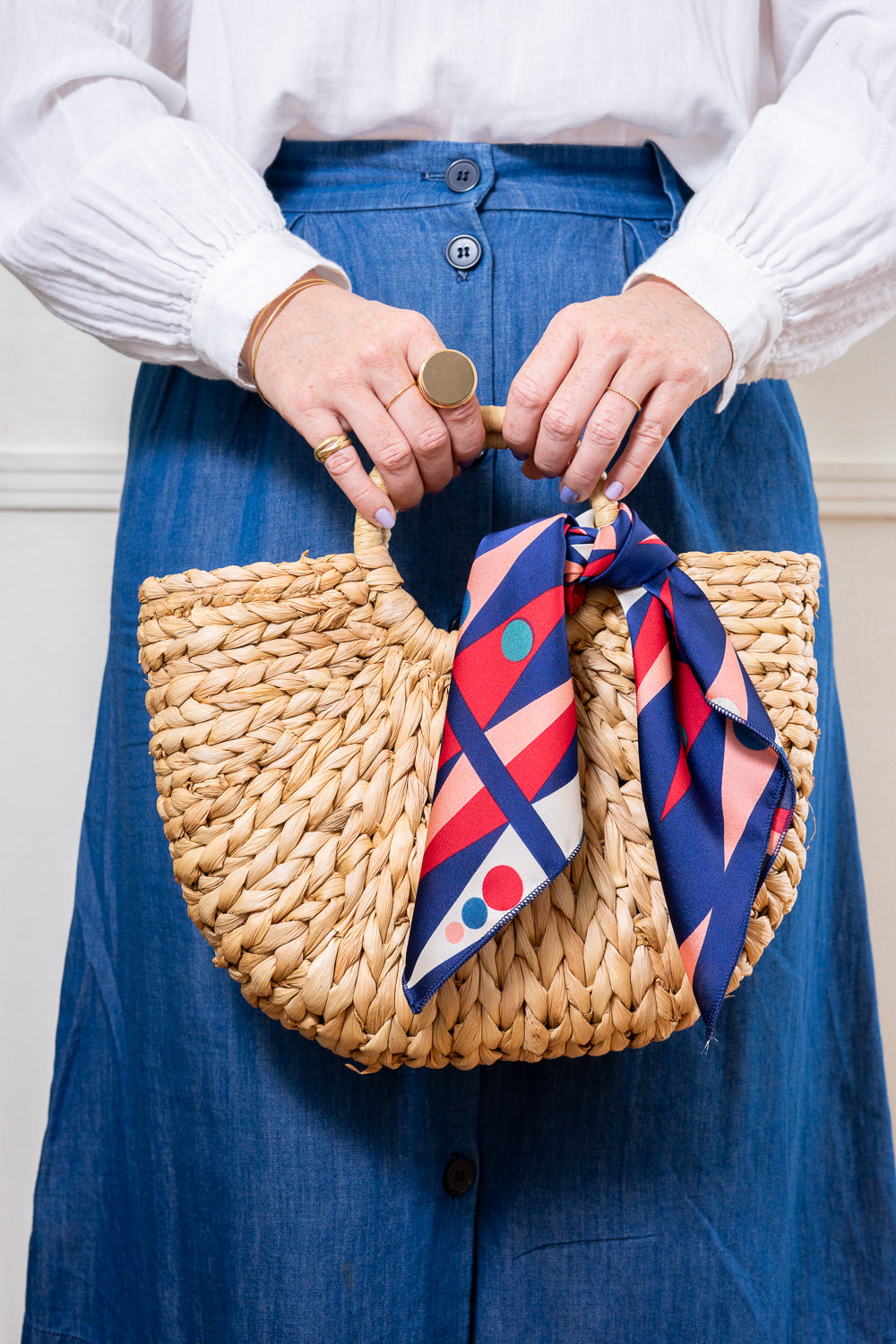 natural raffia straw rattan tote hand bag with red and blue scarf held in hand Janna Conner