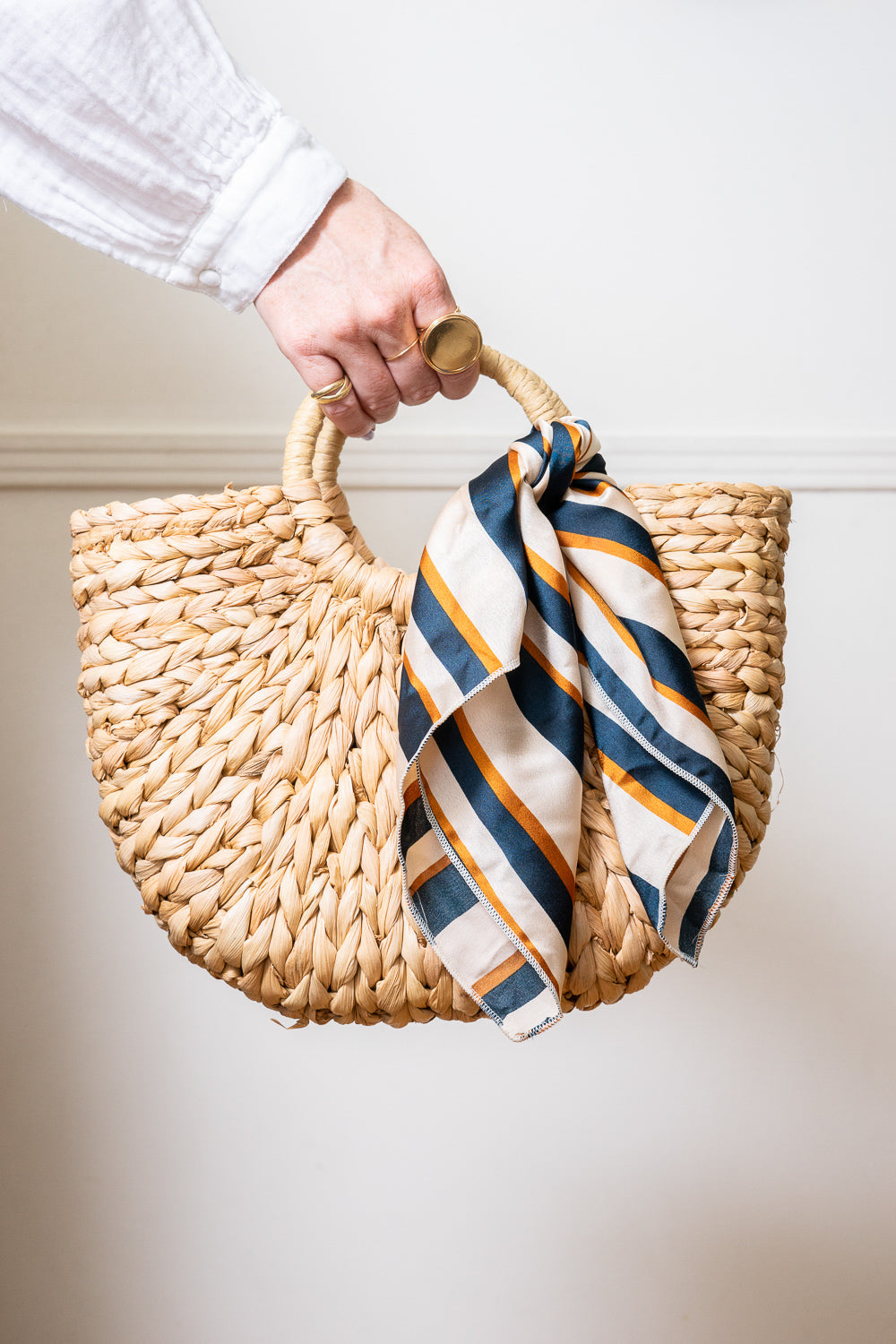 hand holding straw tote hand bag with striped scarf on handle janna conner
