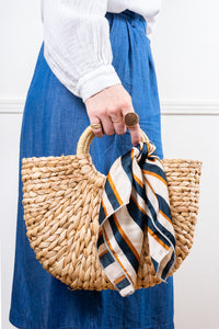 natural raffia straw rattan tote hand bag with navy white yellow striped scarf held in hand Janna Conner