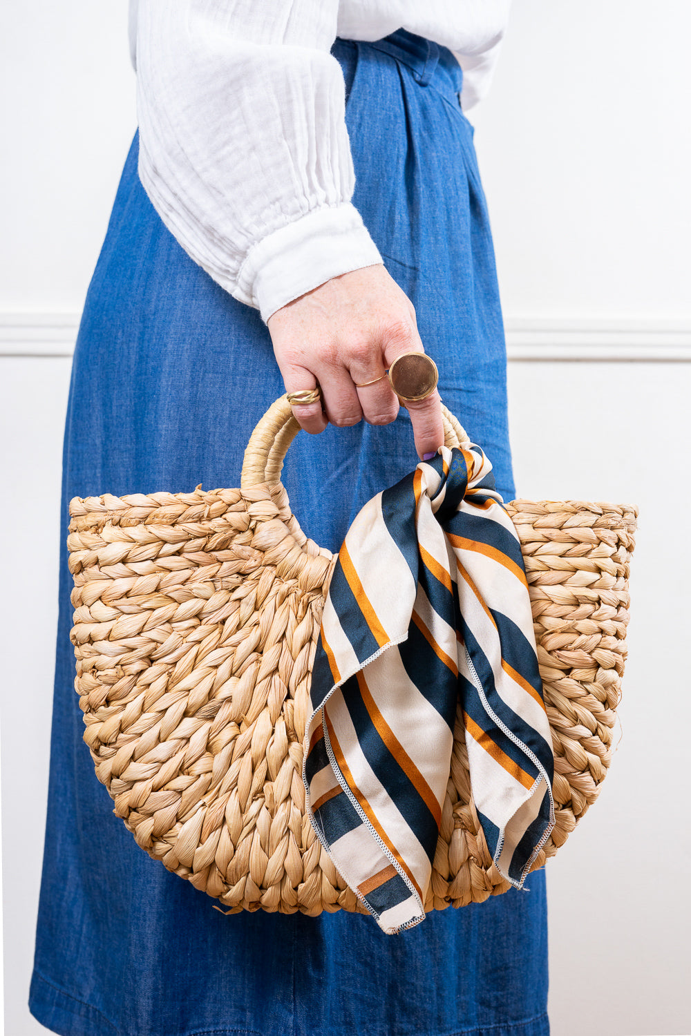 model holding straw tote hand bag with striped scarf tied on handle janna conner