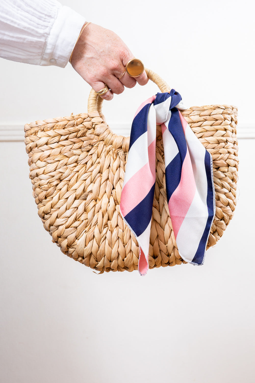 natural raffia straw rattan tote hand bag with pink and blue striped scarf held in hand Janna Conner