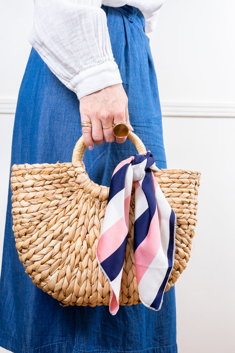 profile holding straw handbag with navy pink white striped scarf tied on held in hand janna conner