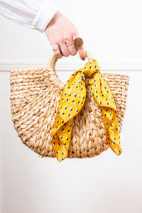 natural raffia straw rattan tote hand bag with yellow scarf held in hand Janna Conner