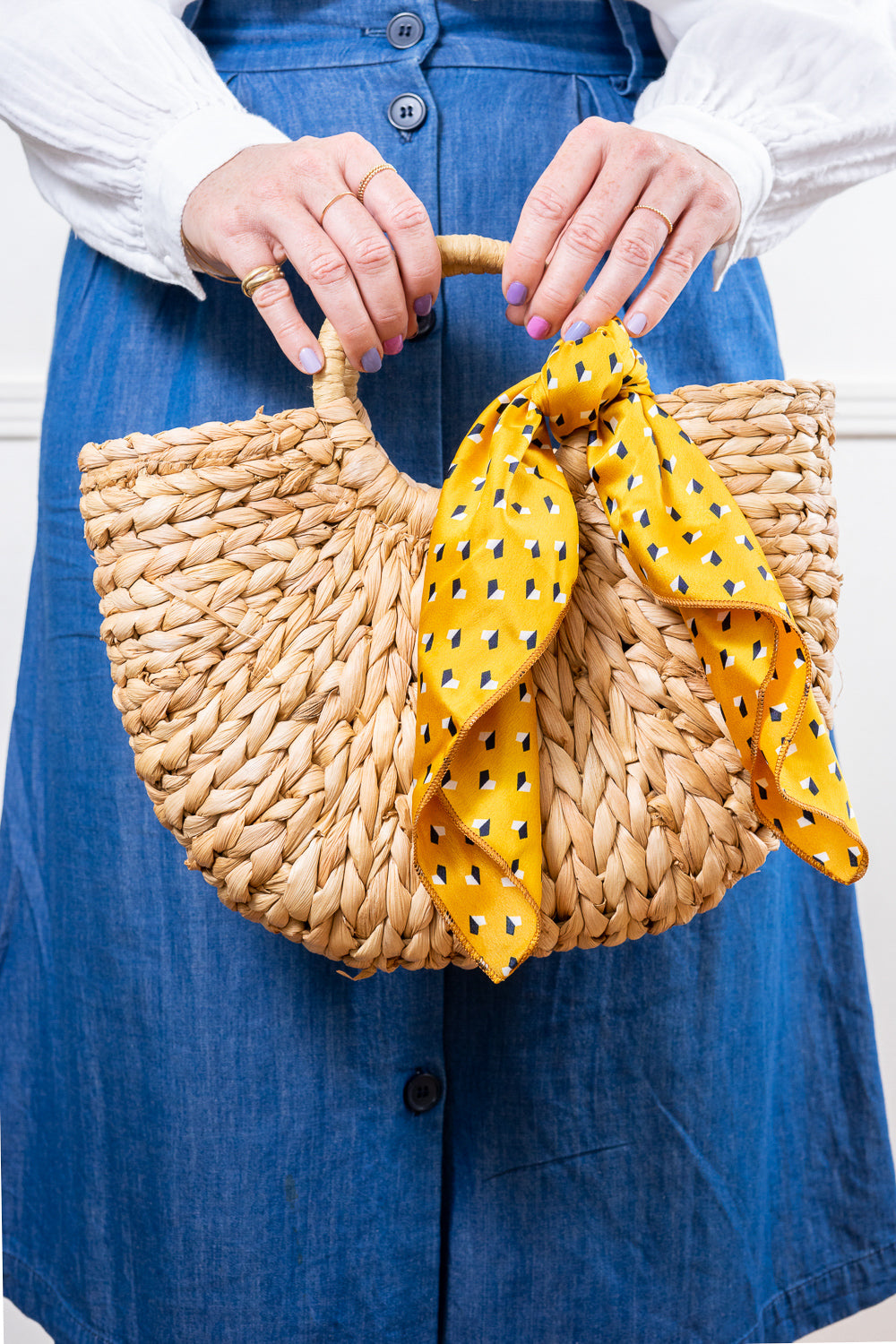 hands holding straw handbag in front of jean skirt tied with yellow print scarf Janna Conner