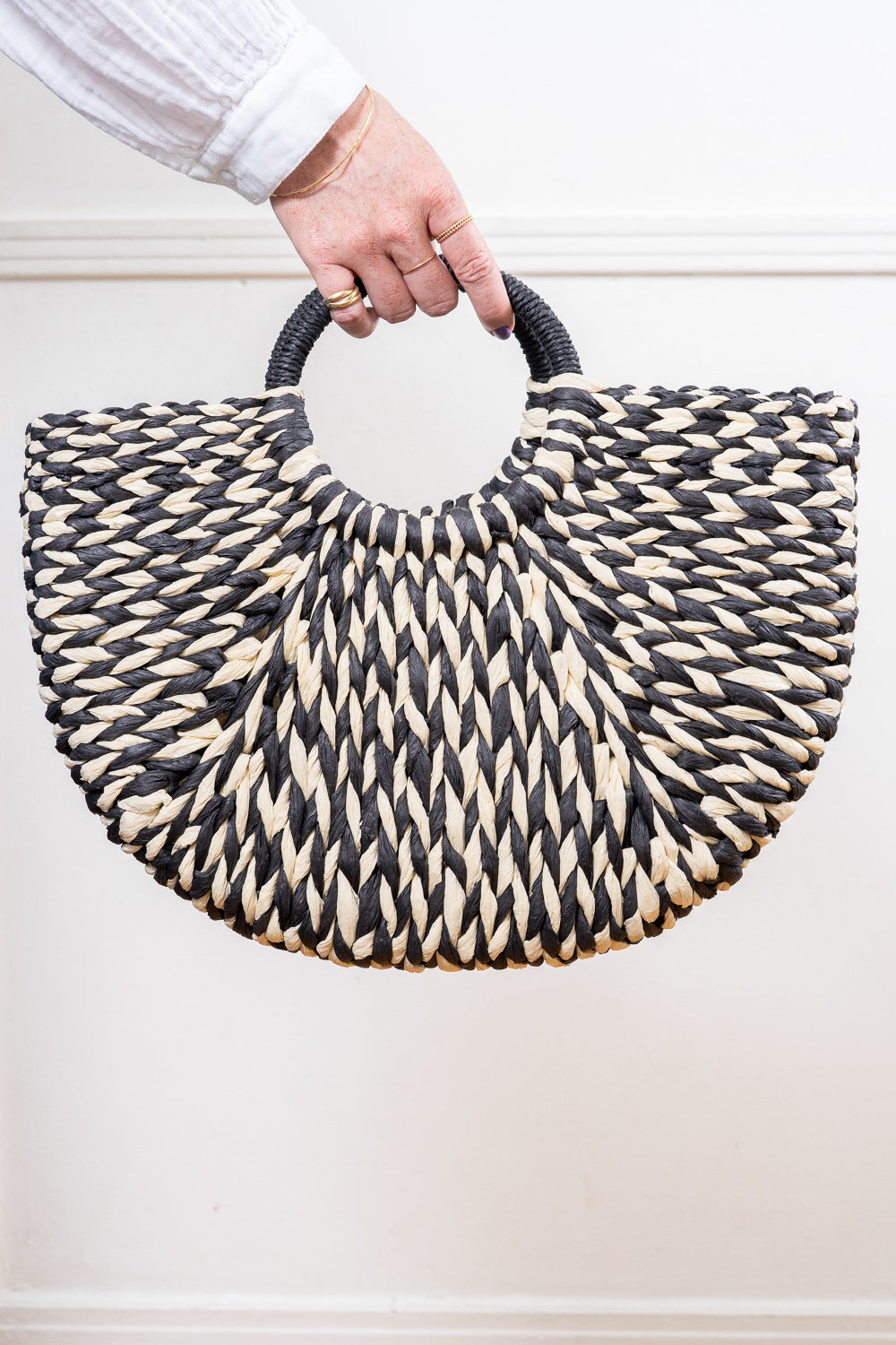 black and white raffia straw tote hand bag held in hand Janna Conner