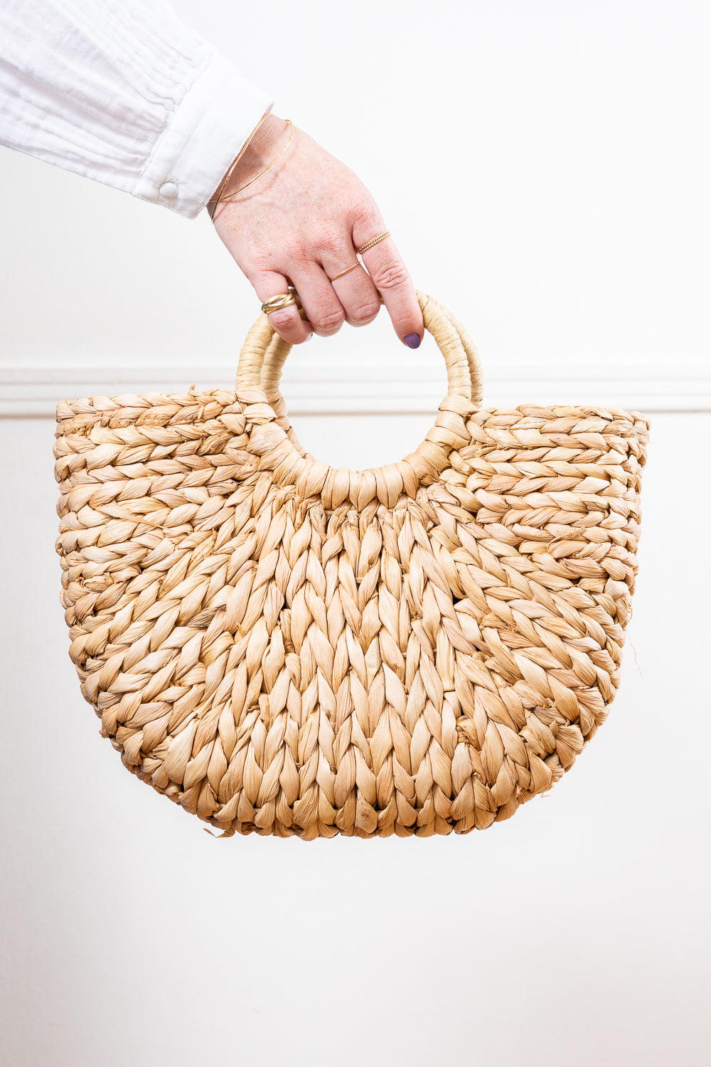 natural raffia straw rattan tote hand bag held in hand Janna Conner