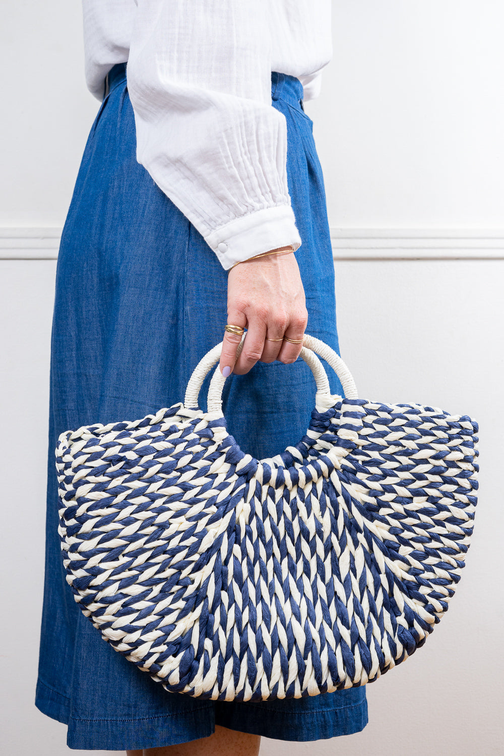 navy and white raffia straw tote hand bag held in hand Janna Conner