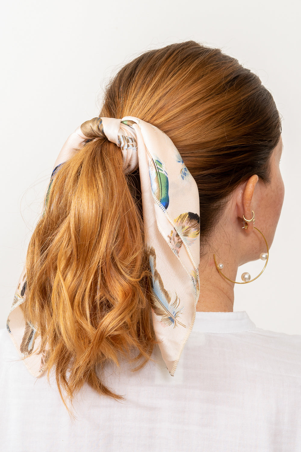 red head model with pale pink print scarf tied in hair ponytail janna conner