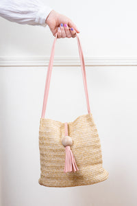 pink tassel straw shoulder bucket bag held in hand janna conner