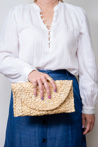 straw clutch purse in model's hand
