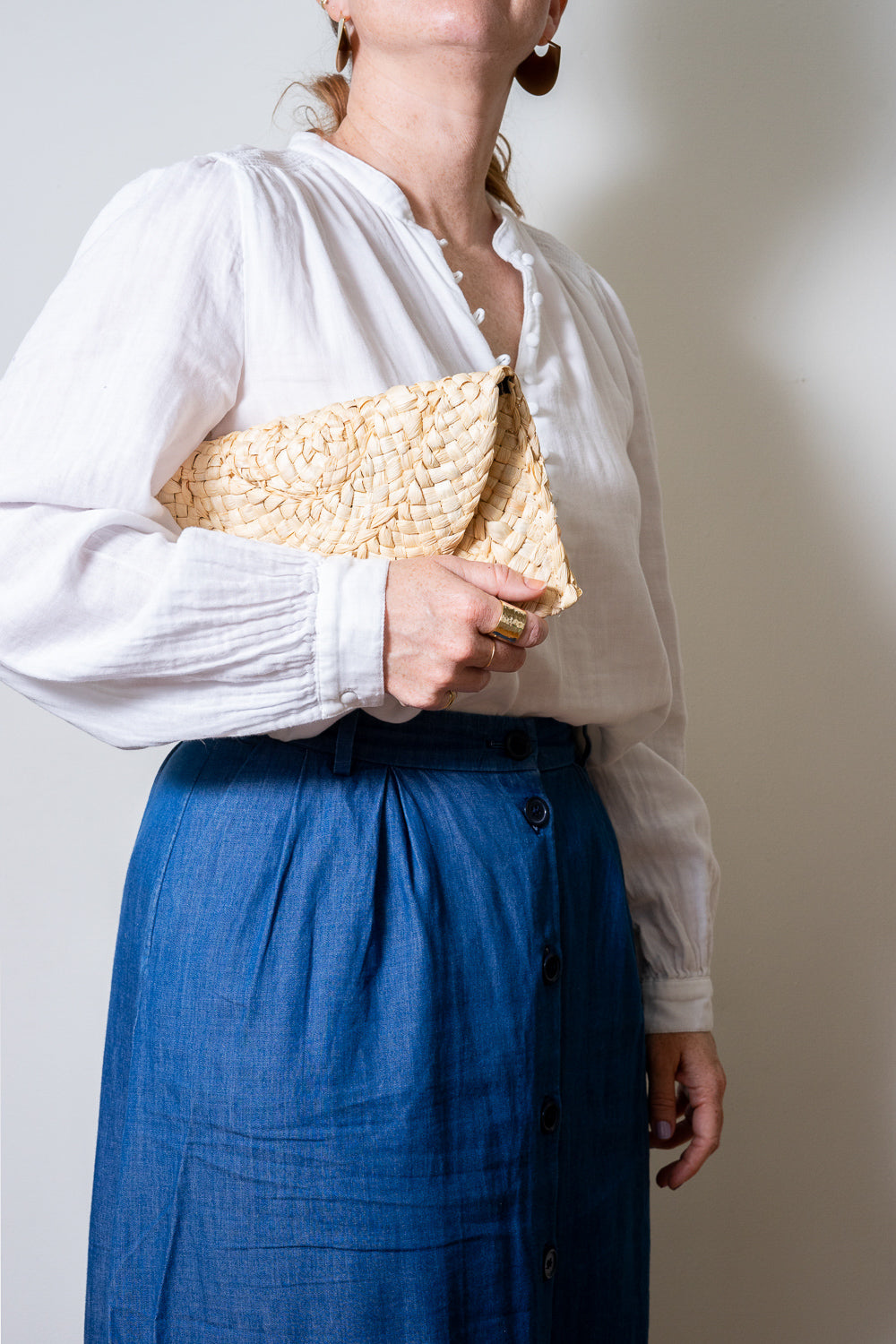 straw clutch purse under model's shoulder