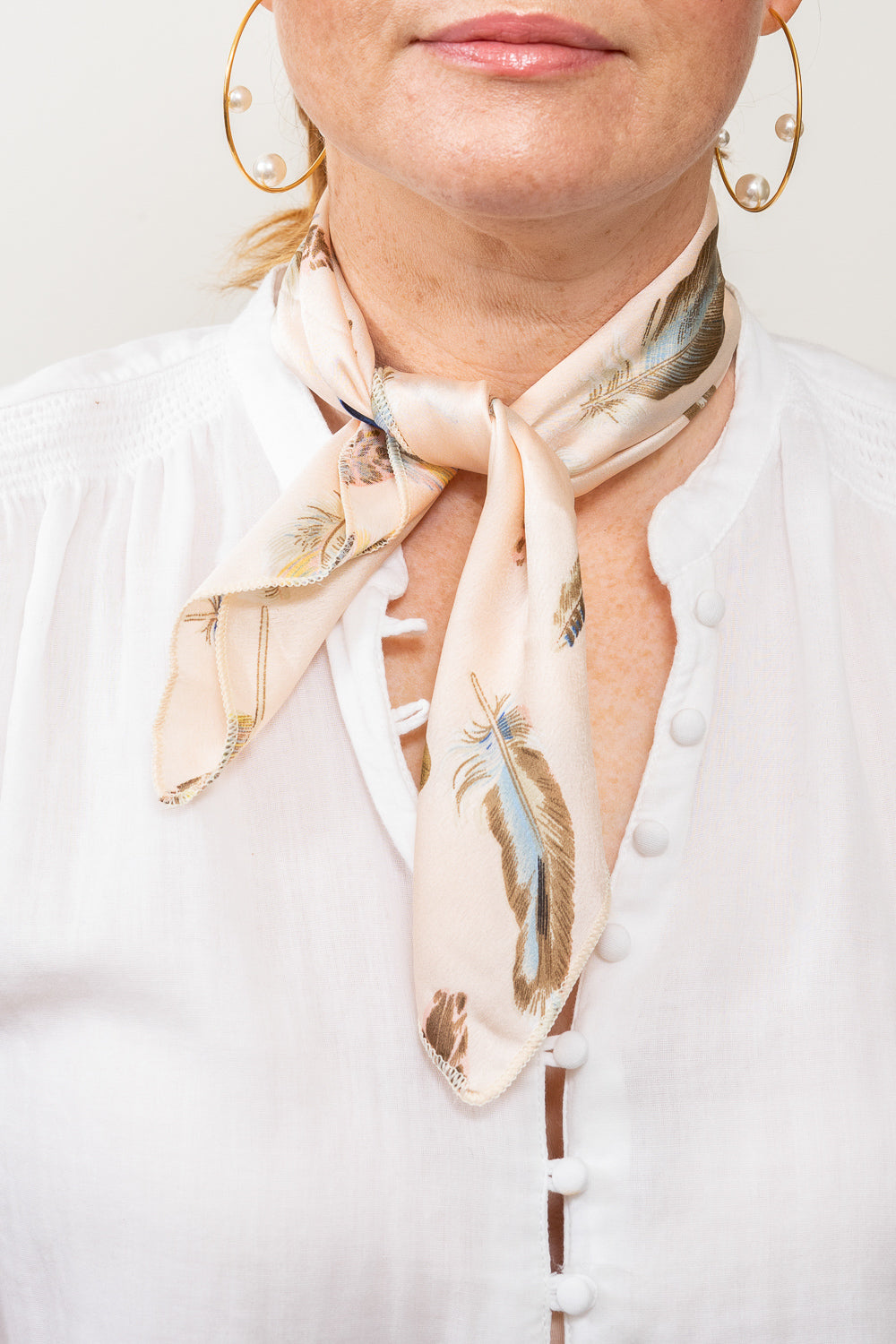 model wearing pale blush neutral feather print neck scarf tied at neck pearl hoop earrings janna conner