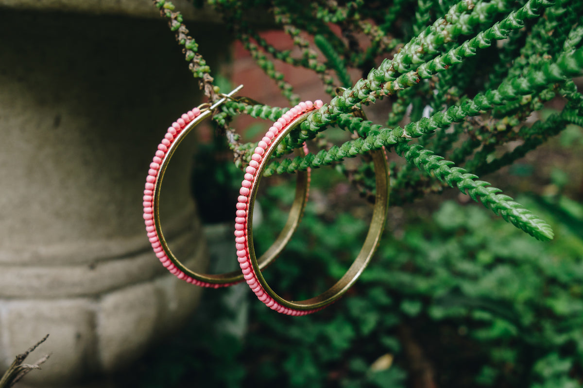 coral beaded hoop earrings by janna Conner on green plant in garden