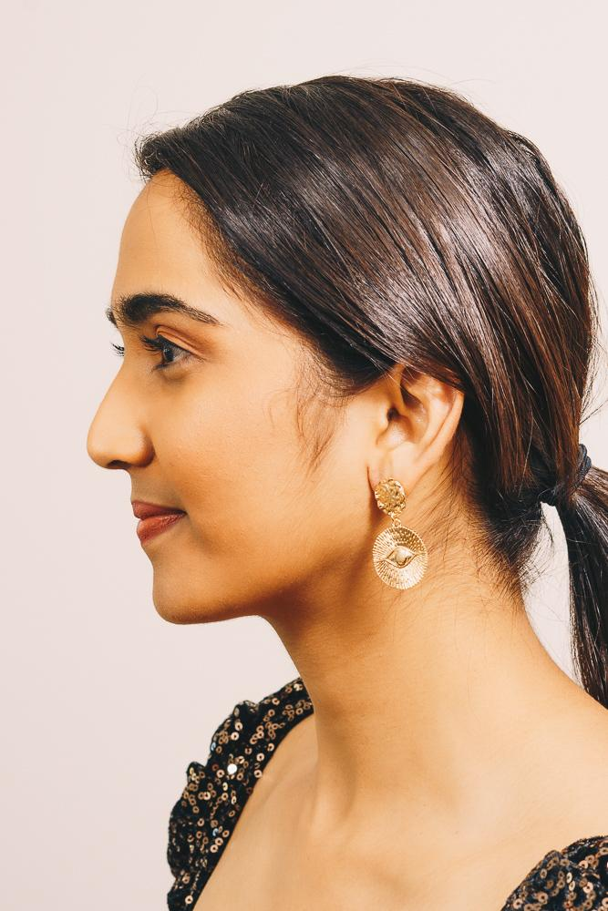 gold coin statement earrings on model
