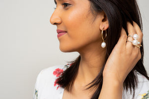 pearl hoop earrings gold Janna Conner on model with pearl stacking rings
