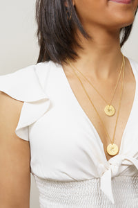 gold starburst coin charm necklaces on model