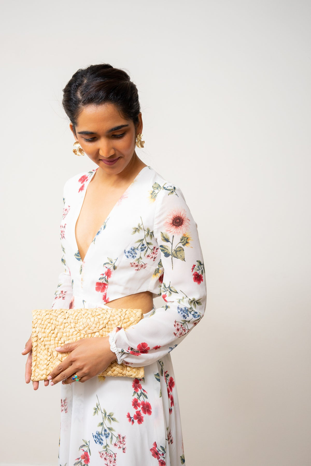 straw clutch purse held by model