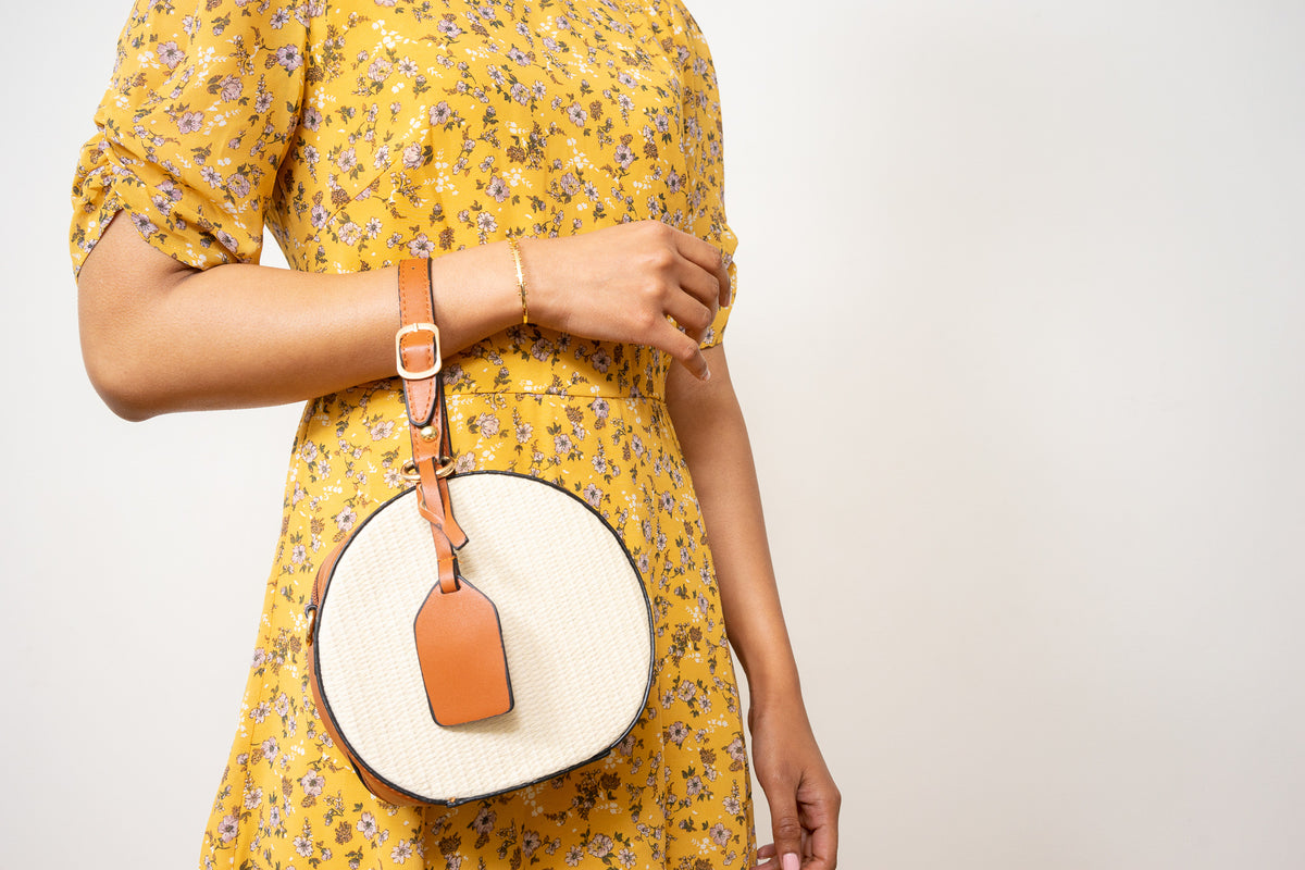 tan and straw wristlet handbag on model's arm