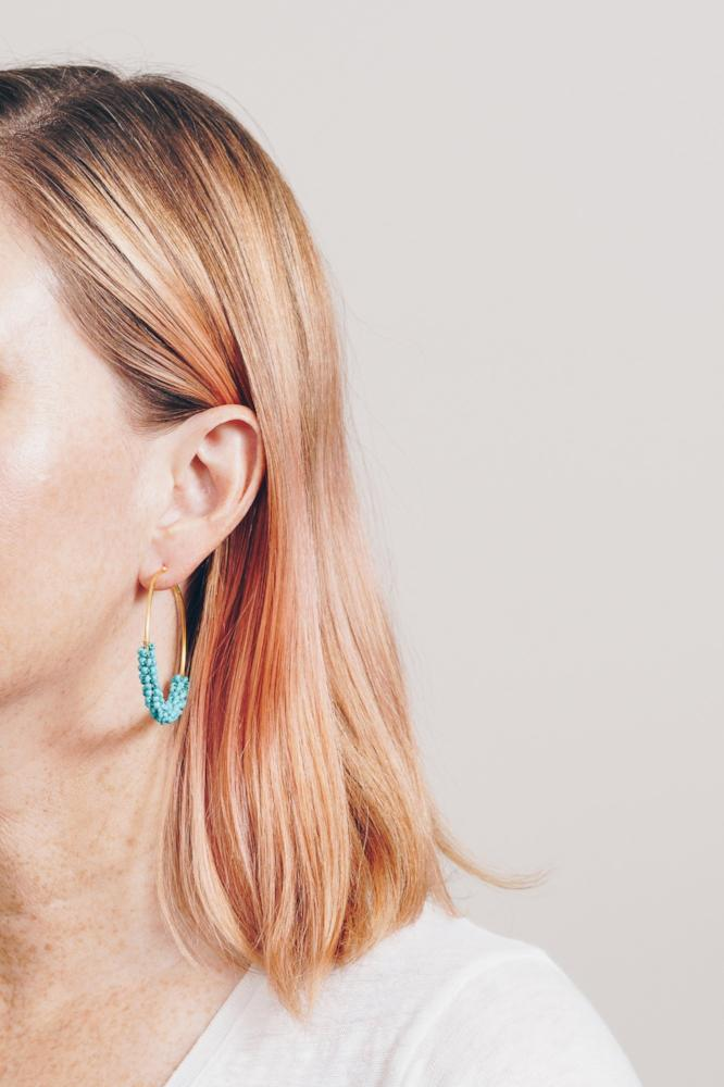 model with pink hair wearing turquoise beaded hoop earrings by janna conner