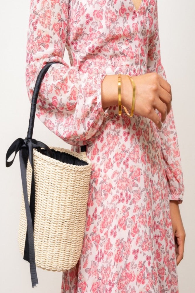 straw bucket bag with black ribbon handle on models arm