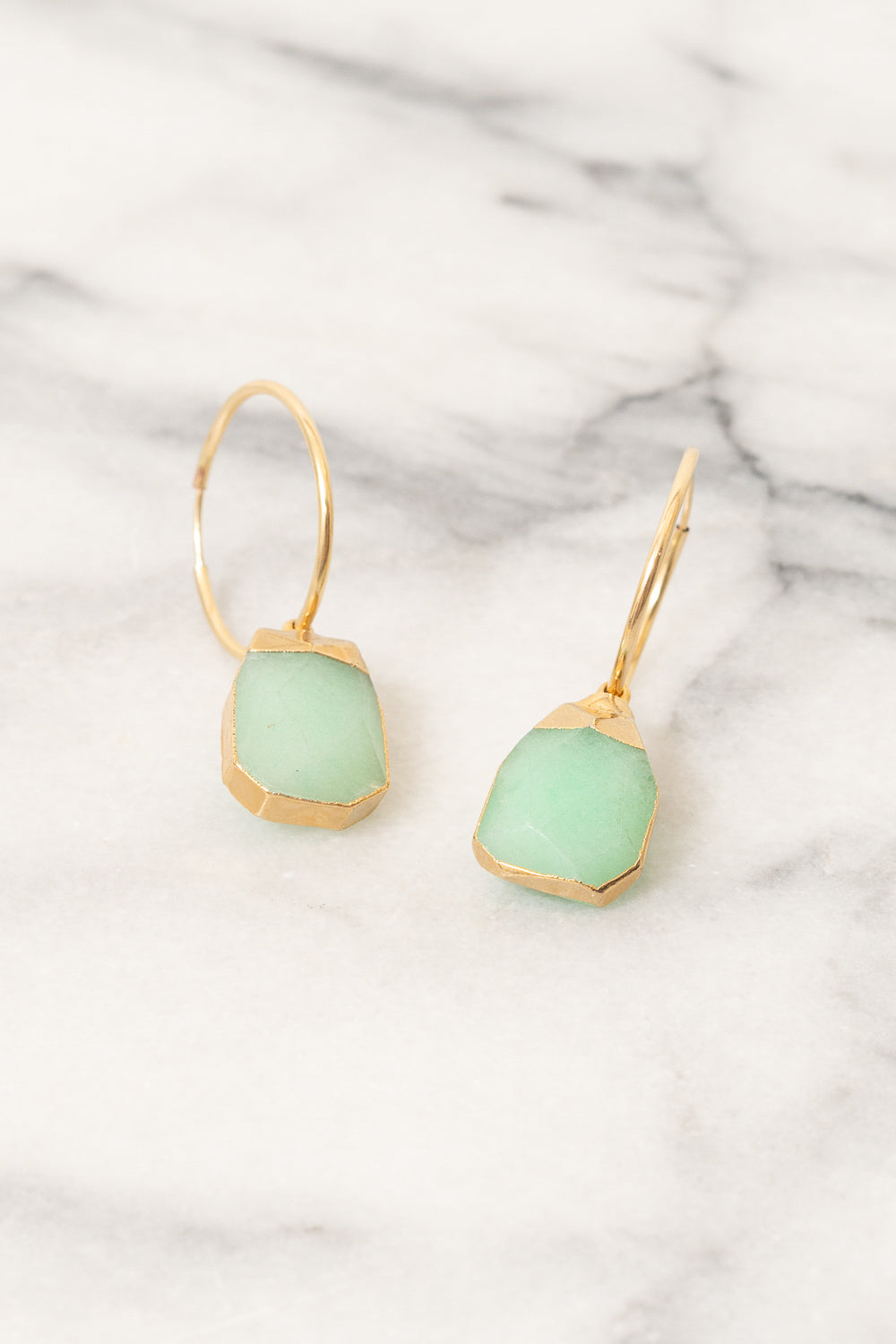 gold hoop earrings with mint jade drop accents on marble