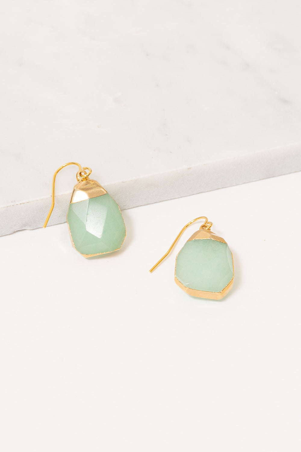 mint jade green dangle earrings on marble