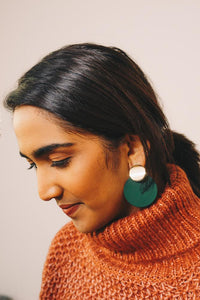 green disc earrings with gold accents on model