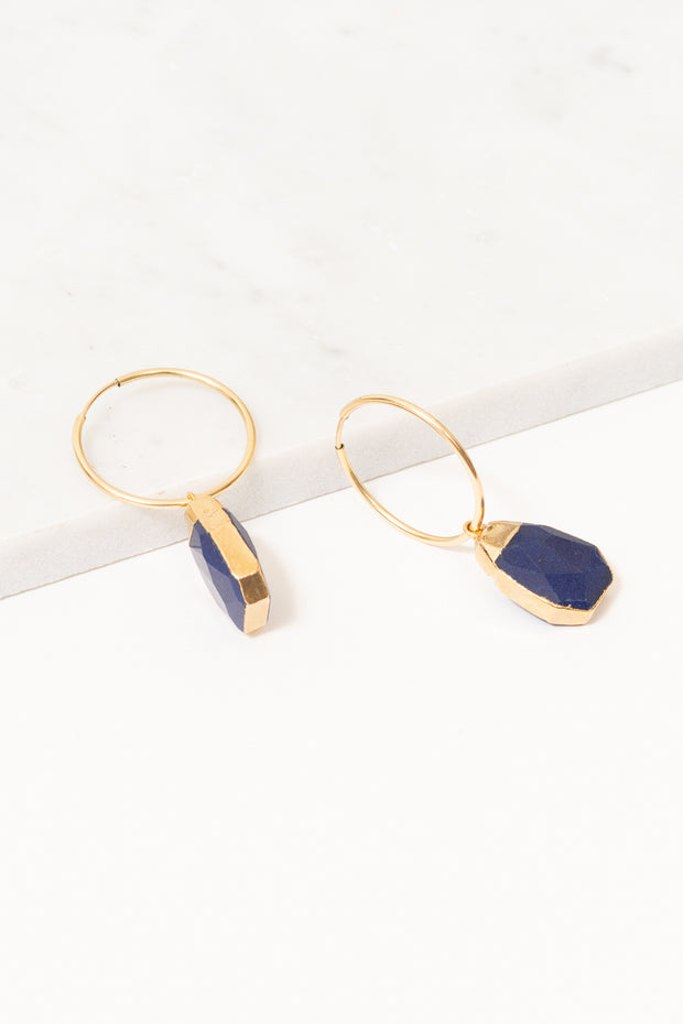 gold hoop earrings with dark blue jade drop accents on marble