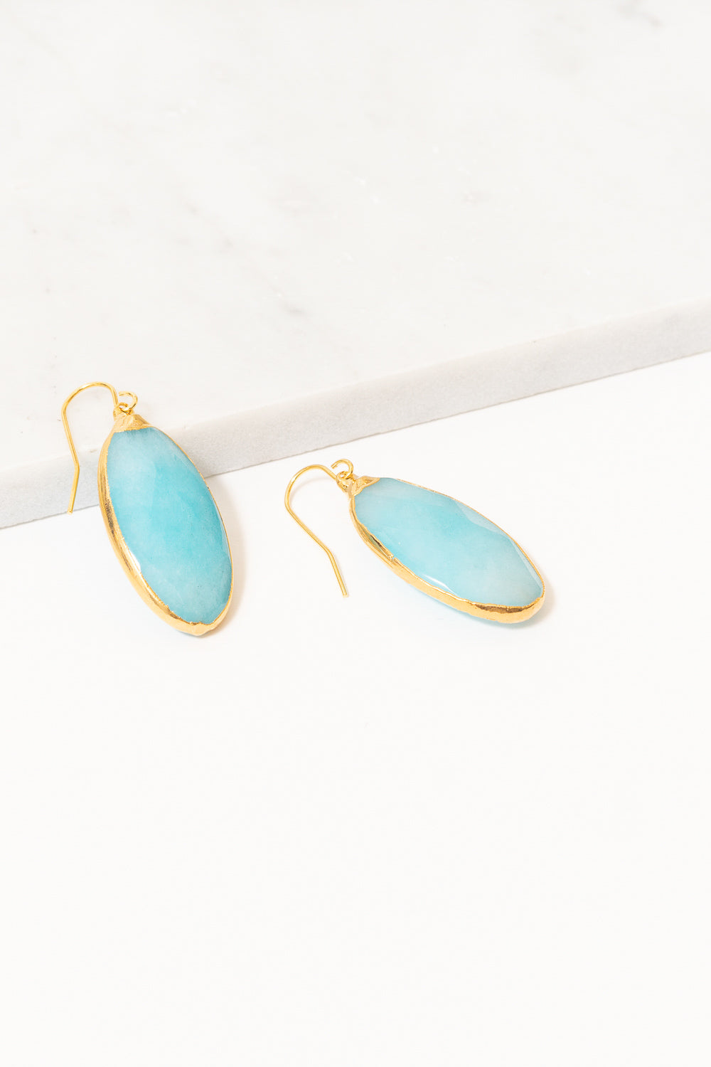 turquoise jade dangle earrings on marble