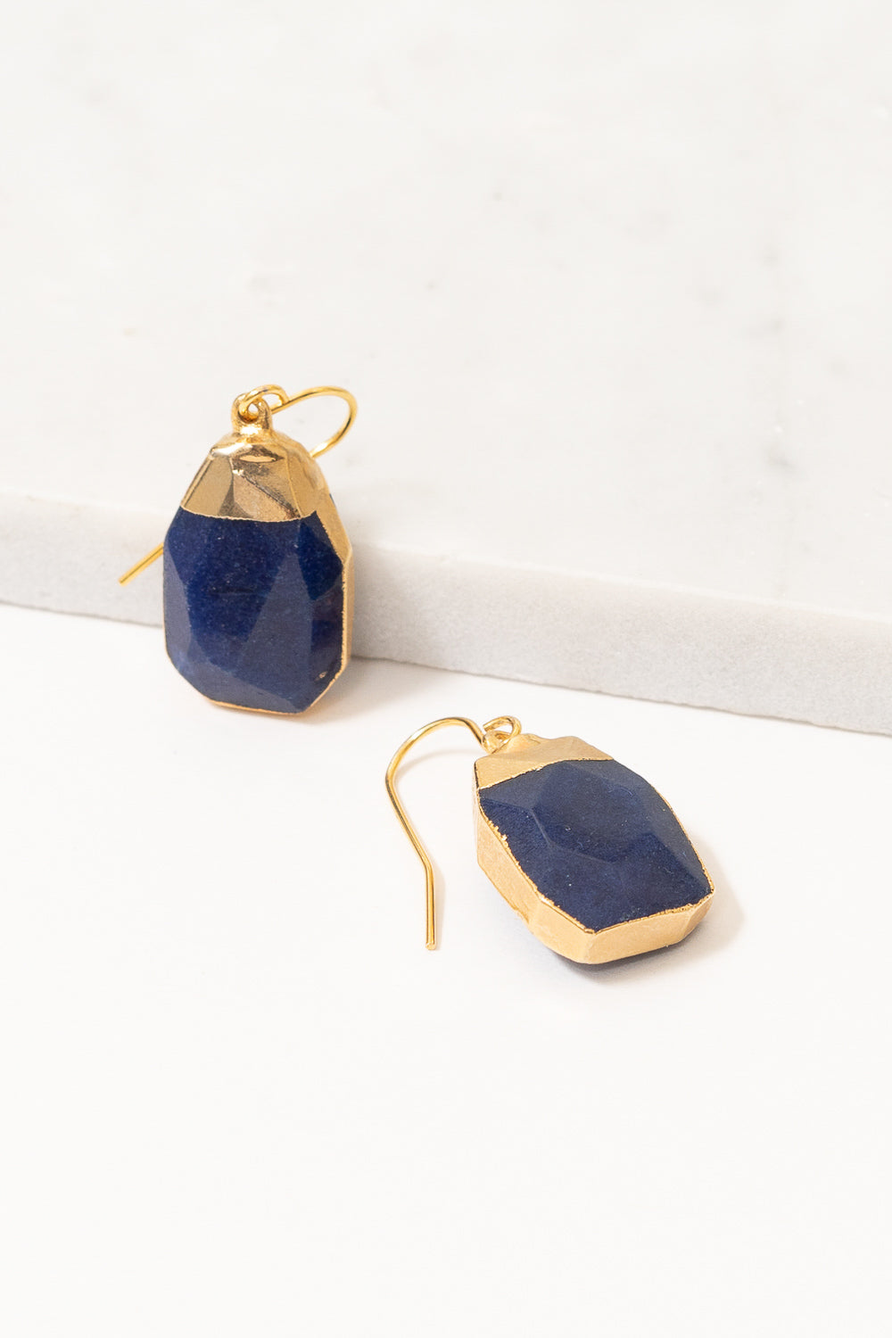 dark blue jade dangle earrings on marble