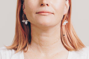 white flower mismatched hoop earrings on model