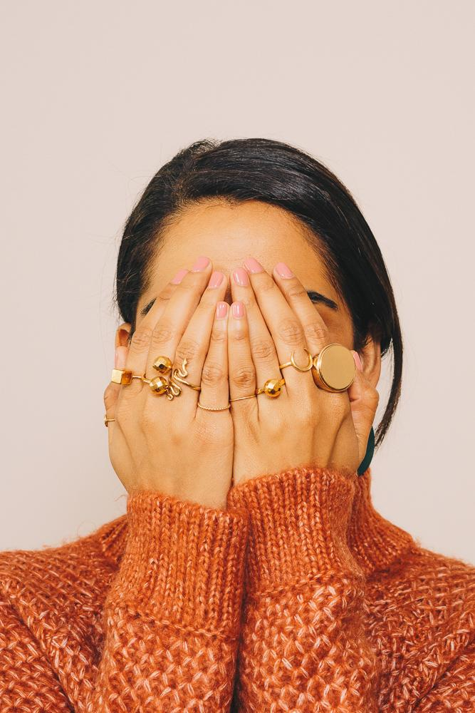 girl hiding face with hands with gold stacking rings