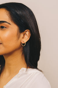 gold curved nail stud earrings on model
