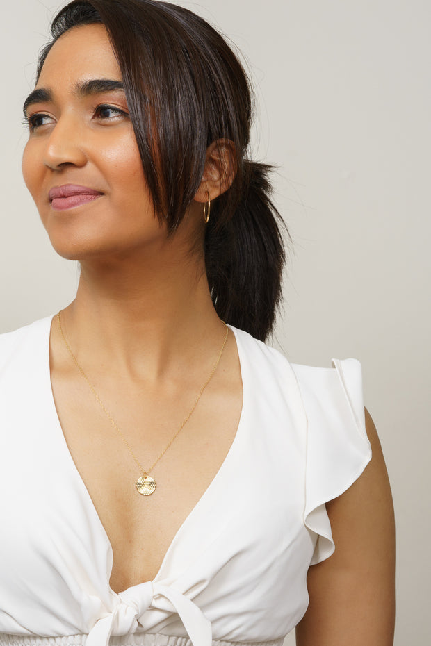 gold honeycomb charm necklace on model