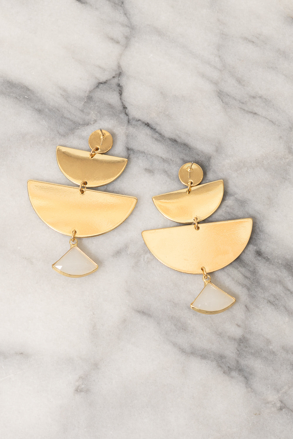 gold fan chandlier earrings on marble