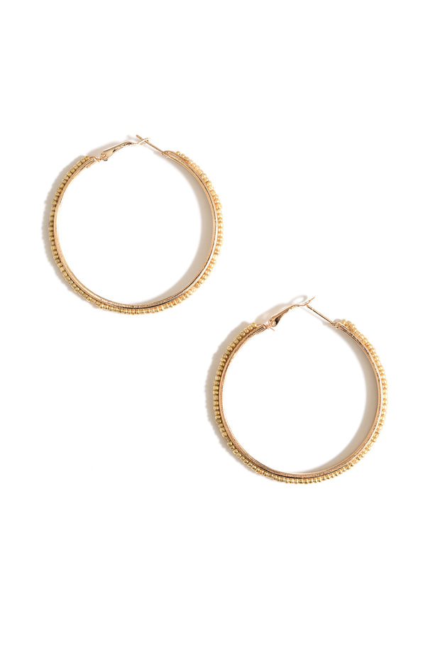 gold beaded hoop earrings by janna Conner on white background