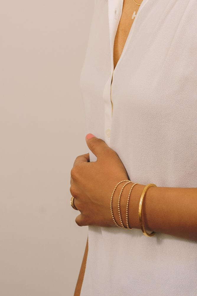 gold beaded bracelets layered with gold cuff bracelet
