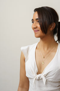 gold droplet pendant necklace and starburst necklace on model
