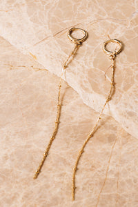 gold delicate earrings on gold huggie hoops