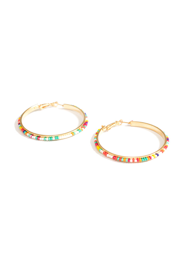 janna Conner rainbow beaded hoop earrings on white background