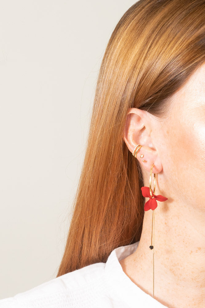 red flower mismatched hoop earrings on model