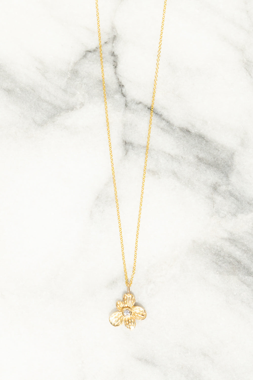 gold flower charm necklace with white sapphire center