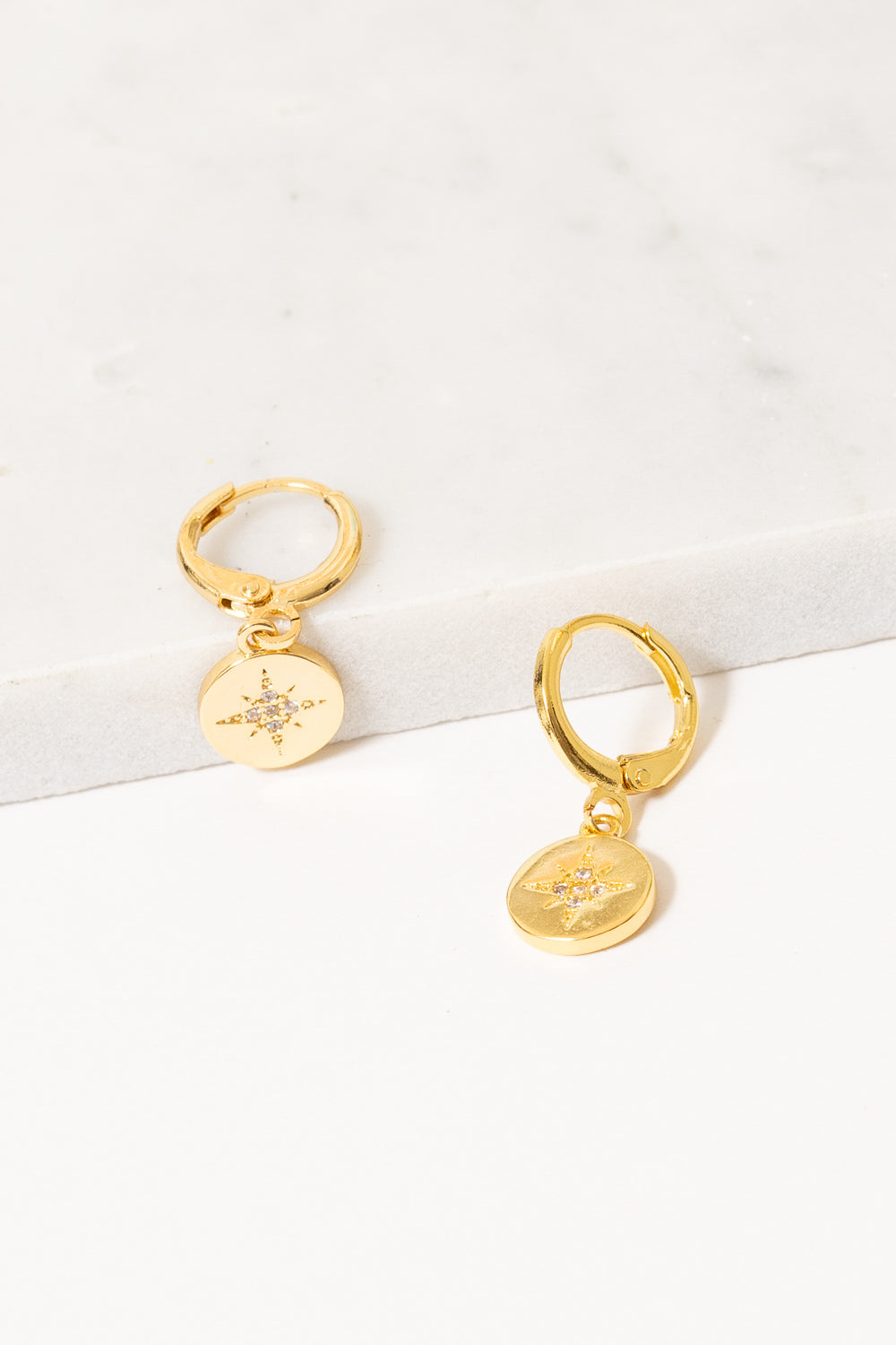 gold huggie hoop earrings with starburst charm dangles by Janna conner