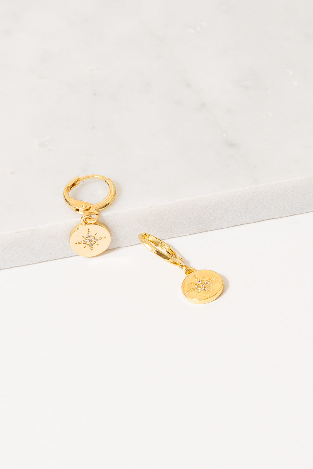 gold huggie hoops with starburst charm dangles by janna conner